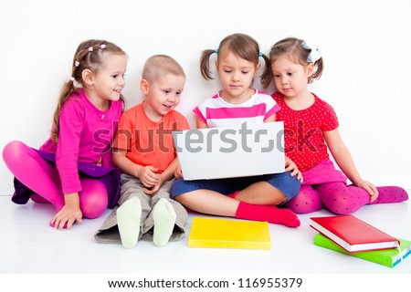 Group of four children working on laptop together - stock photo