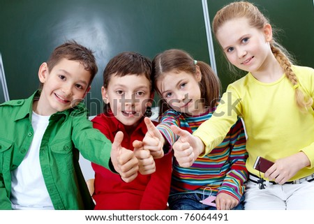 Group of four classmates showing sign of ok - stock photo