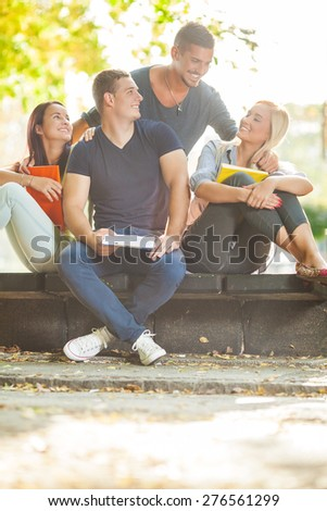 Group of four college students having fun together in a park - stock photo