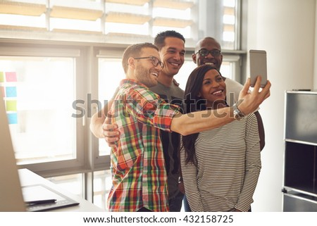 Group of four diverse cheerful co-workers taking self portrait at small office in front of bright windows - stock photo