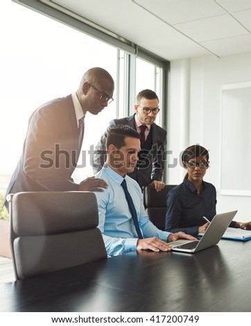 Group of four diverse men and woman seated at conference table with light flare in corner from large window in bright office - stock photo