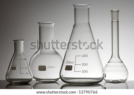 group of four empty laboratory flasks on a white background - stock photo