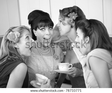 Group of four excited housewives in a kitchen share secrets - stock photo