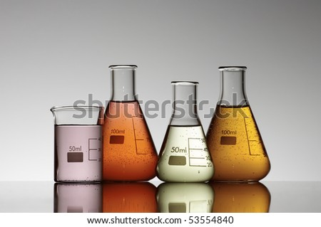 group of four flasks containing brightly colored liquid - stock photo