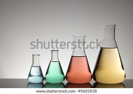 group of four flasks with colored liquid and a white background