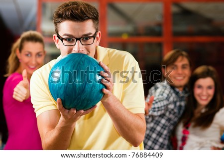 Group of four friends in a bowling alley having fun, three of them cheering the one in charge to throw the bowling ball