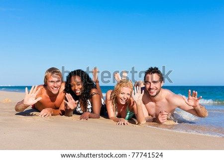 Group of Four friends - men and women - on the beach having lots of fun in their vacation - stock photo