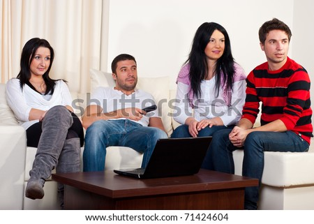 Group of four friends watching tv and sitting comfortable on couch - stock photo