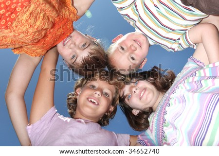 Group of Four Fun Friends Looking Down at the Viewer - stock photo