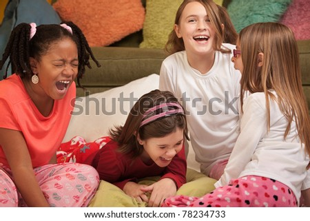 Group of four girls at a sleepover laugh out loud - stock photo