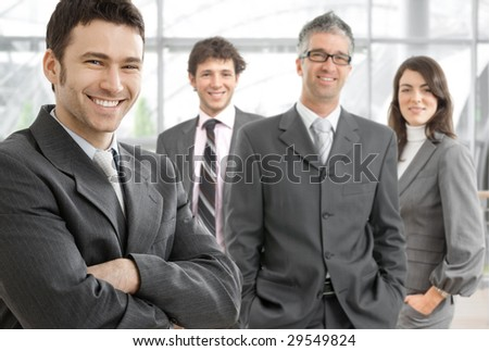 Group of four happy business people wearing gray suit, businessman leading team, smiling. - stock photo