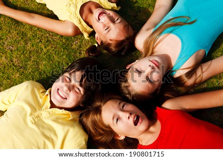 Group of four happy children lying on the grass