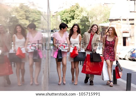 Group of four happy fashionable friends walking on the street smiling and holding colorful shopping bags. - stock photo