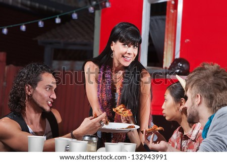 Group of four happy people eating pizza outside - stock photo