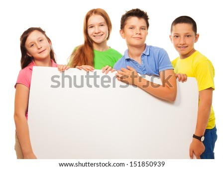 Group of four happy smiling friends, two girls and couple boys, holding blank white sign advertising close portrait - stock photo