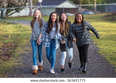 Group of four happy young girls laughing while walking on trail  - stock photo
