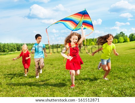 Group of four kids running in the park with kite happy and smiling on summer sunny day - stock photo