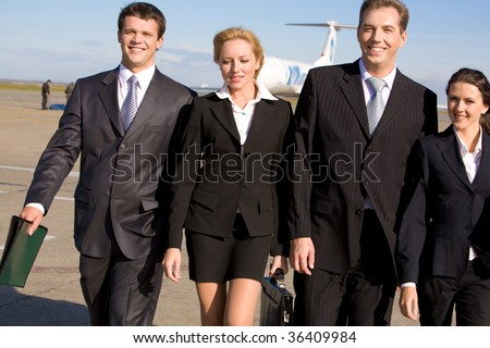 Group of four leaders walking and smiling at camera on the background of airplane - stock photo