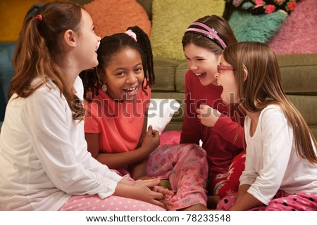 Group of four little girls in pajamas laugh at a sleepover - stock photo
