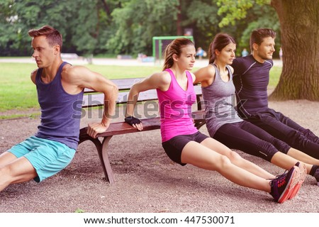 Group of four male and female adults performing dip exercises on park bench outdoors during summer