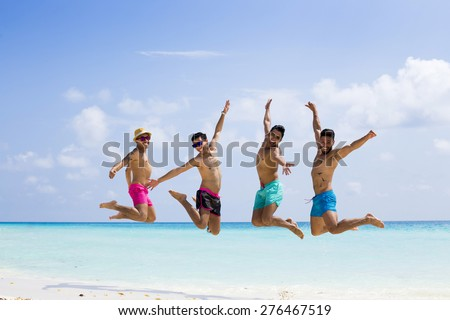 Group of four men jumping at the beach - stock photo