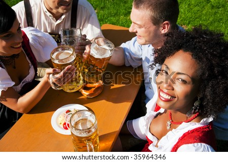 Group of four people in Couple in traditional Bavarian dress, Lederhosen and Dirndl, in a beer garden with Pretzel and Obatzter (traditional cheese) - stock photo
