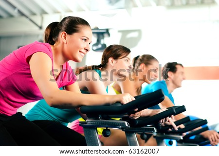 Group of four people in the gym, exercising their legs doing cardio training - stock photo