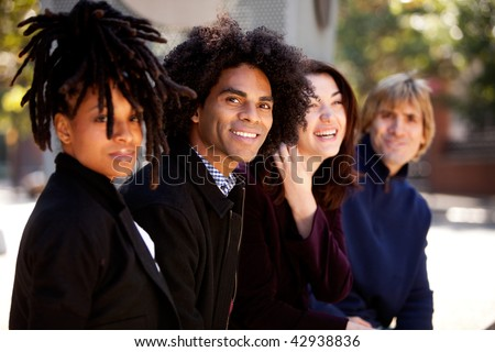 Group of four people of different ethnicities sitting in a row. Horizontally framed shot. - stock photo