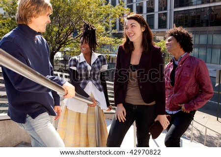 Group of four people of different ethnicities standing by stair railing. Horizontally framed shot. - stock photo