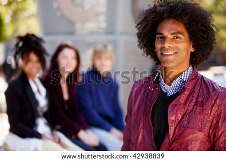 Group of four people of different ethnicities with one man as focus of image. Horizontally framed shot. - stock photo
