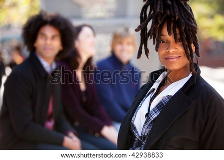 Group of four people of different ethnicities with one woman as focus of image. Horizontally framed shot. - stock photo