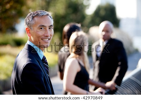 Group of four people with one man as focus. Horizontally framed shot.