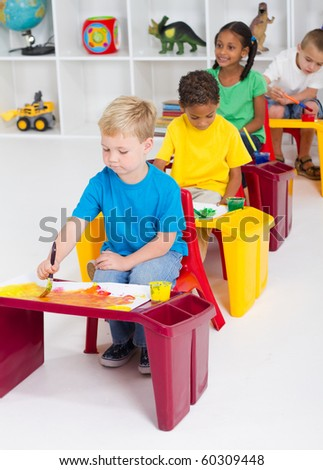 group of four preschool kids in classroom painting picture - stock photo