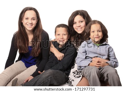 Group of four sibling children, two boys and two girls sitting happily smiling on a white background - stock photo