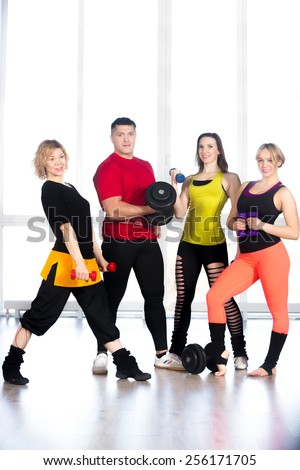 Group of four sporty people holding dumbbells of different sizes, doing weightlifting, bodybuilding exercises. Activity, healthy lifestyle concepts - stock photo