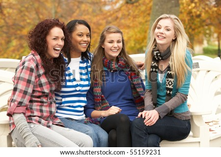 Group Of Four Teenage Girls Sitting On Bench In Autumn Park