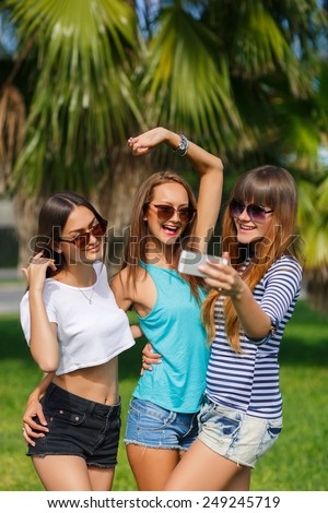 Group Of Four Teenage Girls Taking Picture In summer Park taking selfie photo using smartphone. Portrait of group of peolpe having fun outddors in green summer tropical park - stock photo