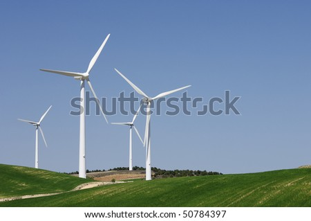 group of four wind turbines on green grass and clear blue sky - stock photo