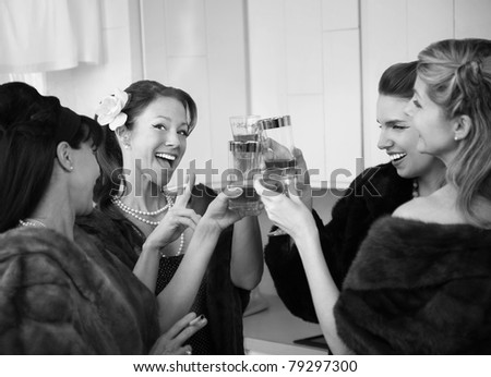 Group of four women with fur coats raising a toast in a kitchen - stock photo