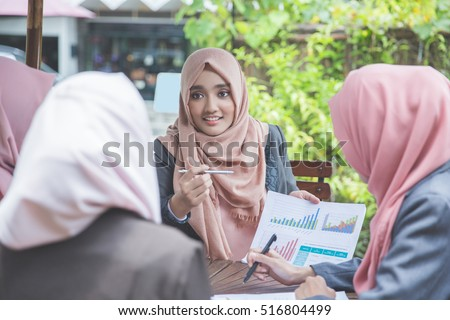 group of four young business woman having a meeting in a coffee shop
