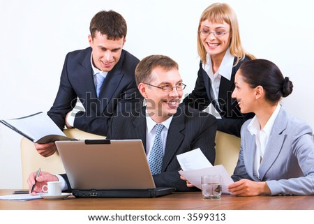 Group of four young businesspeople discussing different questions holding documents gathered together around the table with the laptop, drinks and papers on it - stock photo