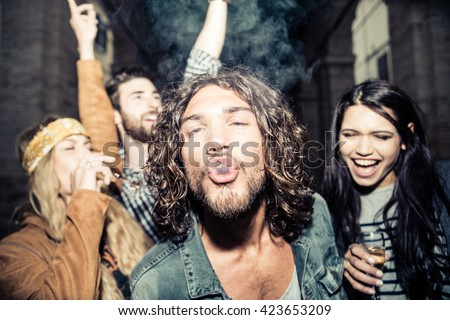 Group of four young friends having party, smoking and drinking alcohol - Best friends clubbing in the night, frontal flash to give realism to the scene - stock photo