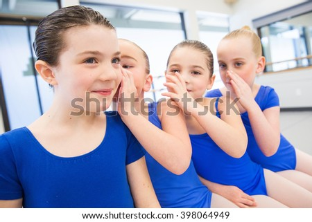 Group of four young girls telling secrets together - stock photo