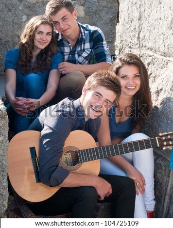 Group of four young happy smiling people with guitar having fun by posing outdoors in spring or summer sitting on the stone staircase. - stock photo