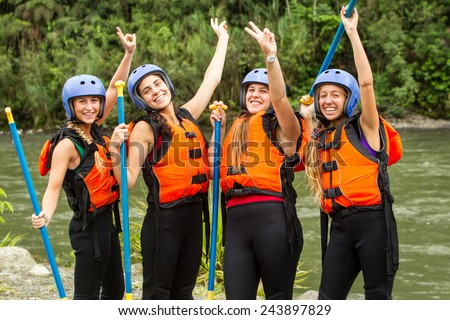 GROUP OF FOUR YOUNG LADIES PREPARED TO GO WHITE WATER RAFTING, WEARING SPECIFIC EQUIPMENT