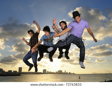Group of four young males jumping against blue sky background - stock photo