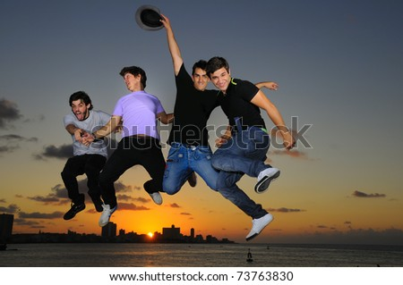 Group of four young males jumping against sunset sky background with happy expression - stock photo