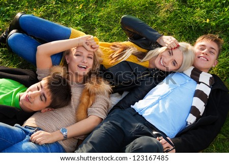 Group of four young people - two couples laying in the grass with smile no their faces - stock photo