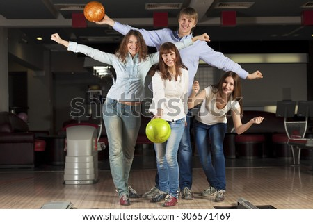 Group of four young smiling people playing bowling - stock photo