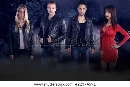 Group of four young vampires in a dark forest